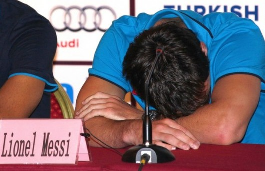 Barcelona player and Argentine international Messi rests his head on his arms during a media conference in Beijing