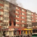 Beijing man hangs off building on fire, falls 3