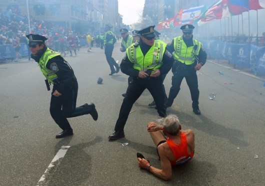 Police officers run with their guns drawn as they hear the second explosion down the street. (John Tlumacki/Globe Staff)