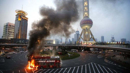 A double-decker tourism bus is seen on fire in from of the Oriental Pearl Tower in the Pudong financial district of Shanghai