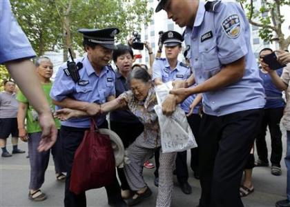 Policemen remove a petitioner outside a court where the trial of disgraced Chinese politician Bo Xilai will be held on Thursday in Jinan