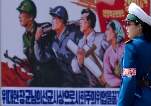 Traffic Officer In Front Of A Propaganda Poster In Pyongyang, North Korea