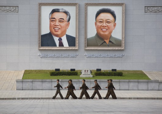 North Korean People's Army Soldiers Passing In Front Of Kim Il Sung And Kim Jong Il Giant Portraits On Kim Il Sung Square, Pyongyang, North Korea