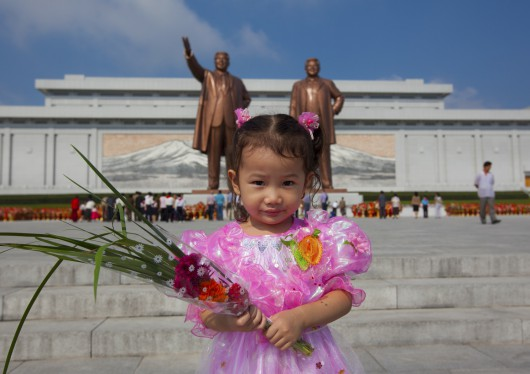Little Girl With Flowers Paying Respect To The Two Statues Of The Dear Leaders In Grand Monument Of Mansu Hill, Pyongyang, North Korea