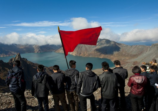 Group Of Students With Red Flag In Front Of Lake At Mount Baekdu, North Korea