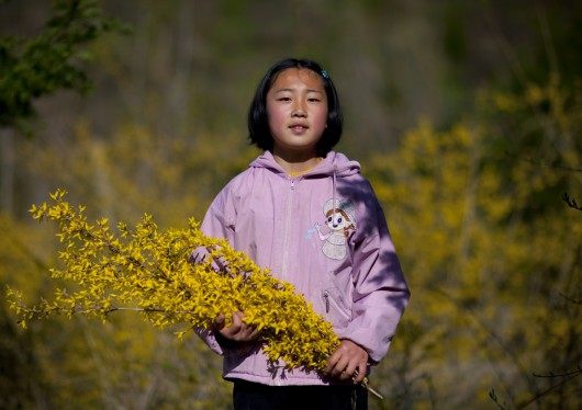 Girl With Flowers In Jung Pyong Ri Village, North Korea
