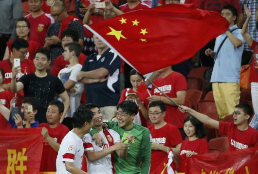 China's Hao Junmin, China's Zheng Zhi and China's goalkeeper Wang Dalei celebrate their win over Uzbekistan after their Asian Cup Group B soccer match at the Brisbane Stadium in Brisbane