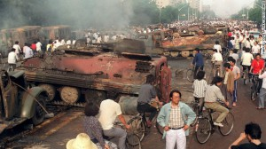 Residents gather next to burnt-out tanks in the aftermath of the crackdown