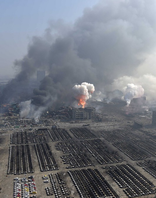 An aerial picture of smoke rising at the site of the explosions is seen at the Binhai new district, Tianjin